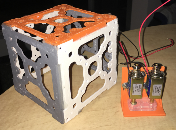 Solenoid mount with Iteration #3 and solenoids compared to a 1u cubesat