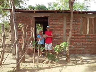 Residents of El Sauce, Nicaragua stand next to their home built by The 4 Walls Project